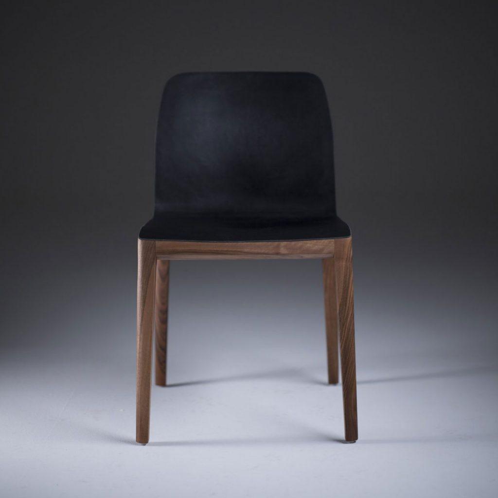 Silla Invito en madera y cuero negro, con acabados suaves y modernos, realizada artesanalmente en Europa